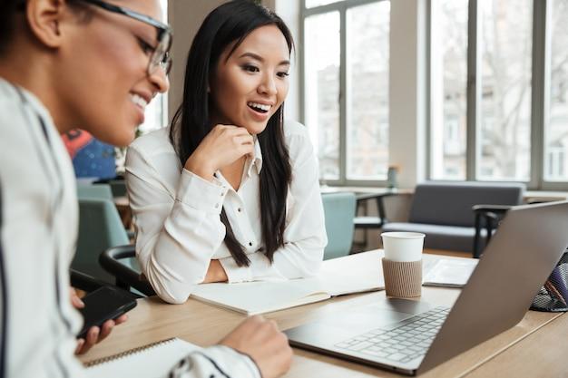 Gelukkige opgewekte jonge bedrijfsvrouwen die laptop computer met behulp van.