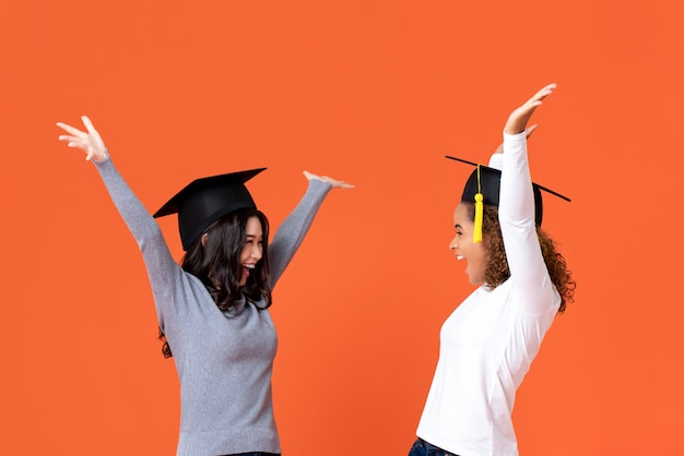 Gelukkige opgewekte jonge vrouwelijke studenten die gediplomeerde kappen dragen die met handen glimlachen die vierend die graduatiedag opheffen op oranje muur wordt geïsoleerd