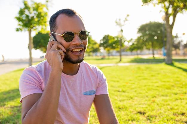 Gelukkige opgewekte latijnse kerel die in zonnebril op mobiele telefoon spreekt