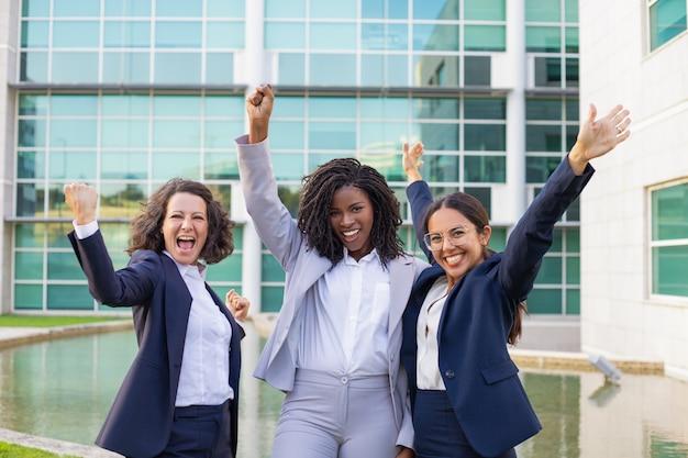 Gelukkige opgewekte onderneemsters die zich bij bedrijfssucces verheugen