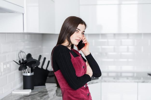 Gelukkige opgewekte vrouw die op mobiele telefoon spreekt alvorens in een keuken te koken
