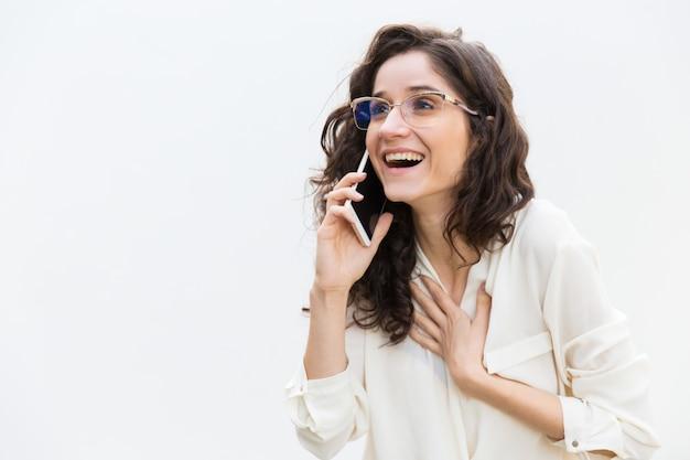 Gelukkige opgewekte vrouw in glazen die op cellphone spreken