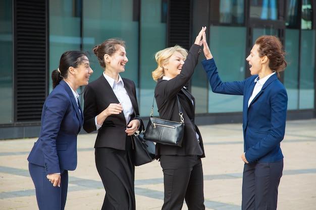 Gelukkige opgewonden bedrijfsdames die high five geven. onderneemsters die pakken dragen die in stad samenkomen, die succes vieren. teamsucces en teamwerkconcept