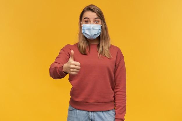 Gelukkige opgewonden jonge vrouw in virusbeschermend masker op gezicht tegen coronavirus die duimen toont die omhoog over gele muur worden geïsoleerd
