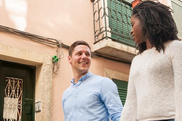 Gelukkige opgewonden kaukasische kerel in liefde met zijn zwarte vriendin