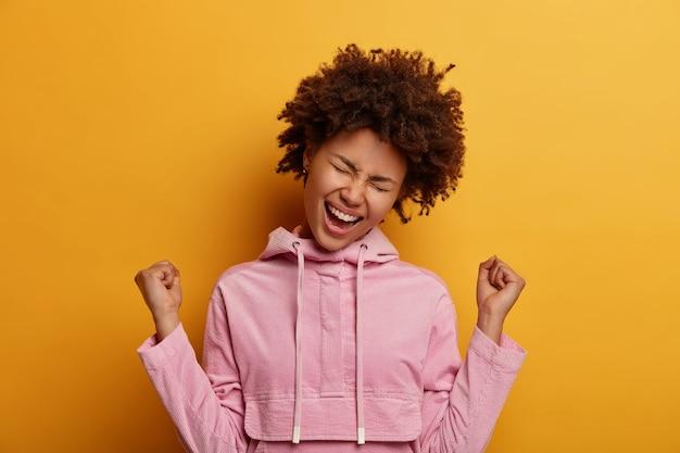 Gelukkige opgewonden mooie vrouw balt vuisten, roept hoera, viert goed nieuws, kantelt het hoofd, kleedt nonchalant, draagt roze hoodie, geniet van zoet succes, voelt de smaak van overwinning, draagt fluwelen sweatshirt