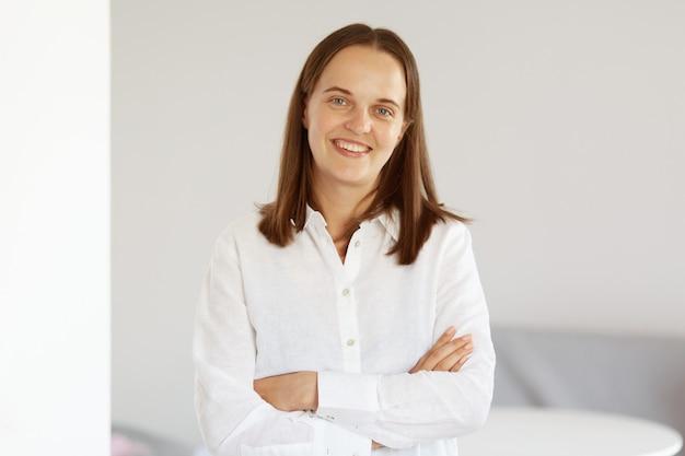 Gelukkige, optimistische, innemende vrouw met een aangename uitstraling, gekleed in een wit casual stijlshirt dat met gekruiste handen staat, vertrouwen uitdrukt, naar de camera kijkt.