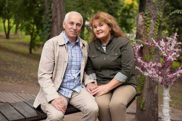 Gelukkige oude bejaarde kaukasische paar lachend in park op zonnige dag, senior paar ontspannen in de lente herfst tijd.