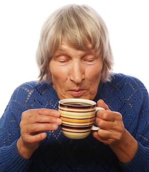 Gelukkige oude dame met koffie, die op wit wordt geïsoleerd