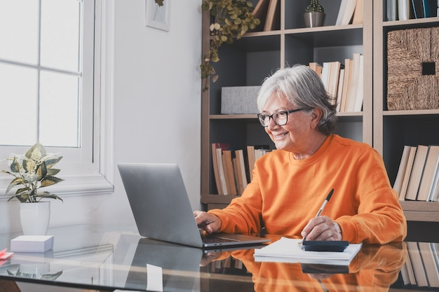 Gelukkige oude kaukasische zakenvrouw glimlachend online werken kijken naar webinar podcast op laptop en leren onderwijs cursus conferentiegesprekken maken aantekeningen zitten op het werk bureau, e-learning concept