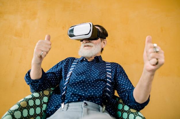 Gelukkige oude man met een goed verzorgde baard die zijn duimen toont terwijl hij een virtual reality-bril gebruikt om film te kijken. studio die op gele achtergrond is ontsproten. vr-technologieën