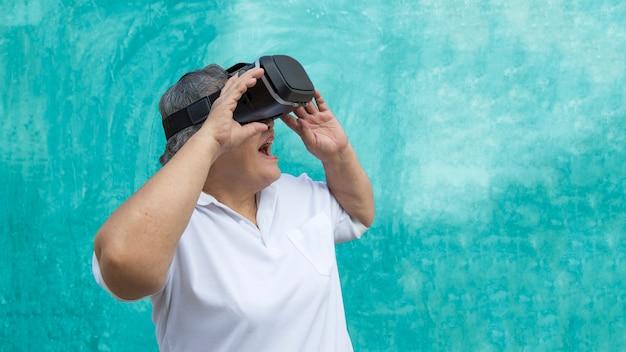 Gelukkige oude ouder gebruikt vr virtual reality-glas op de muur