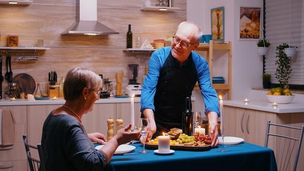 Gelukkige oude senior man die zijn vrouw bedient met druiven en kaas. bejaard oud echtpaar praten, aan tafel zitten in de keuken, genieten van de maaltijd, hun jubileum vieren in de eetkamer