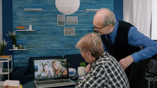 Gelukkige oude senior paar grootouders zwaaien op laptopcomputer tijdens videoconferentie bellen, genieten van sociale afstandsdiscussie, virtuele familiebijeenkomst online chatten met kleinkinderen thuis