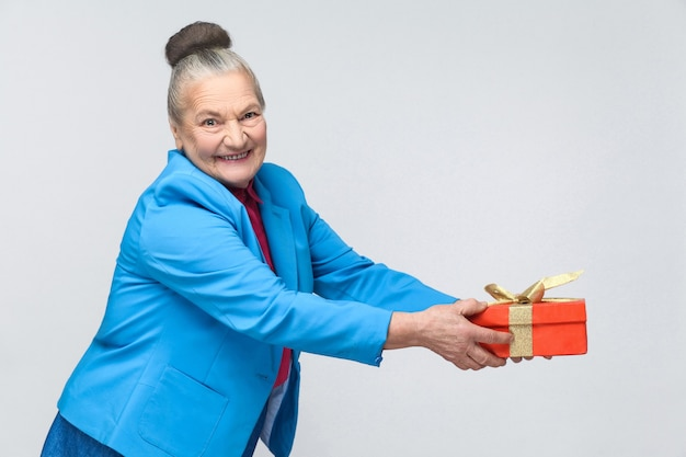Gelukkige oude vrouw die een geschenkdoos vasthoudt en deelt