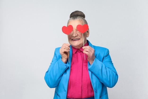 Gelukkige oude vrouw die twee rood klein hartteken houdt