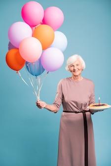 Gelukkige oude vrouw in elegante jurk met taart met kaars en bos van kleurrijke ballonnen