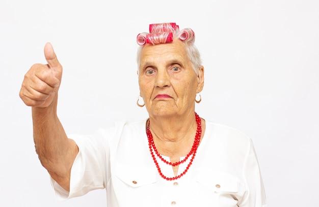 Gelukkige oude vrouw met omhoog duimen. geïsoleerd op witte achtergrond