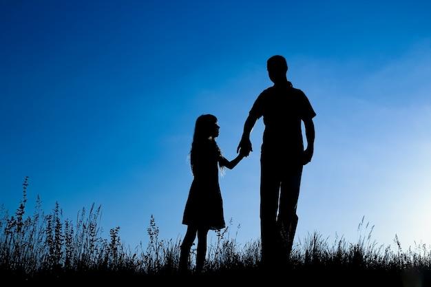 Gelukkige ouder met kind in het silhouet van het park in openlucht