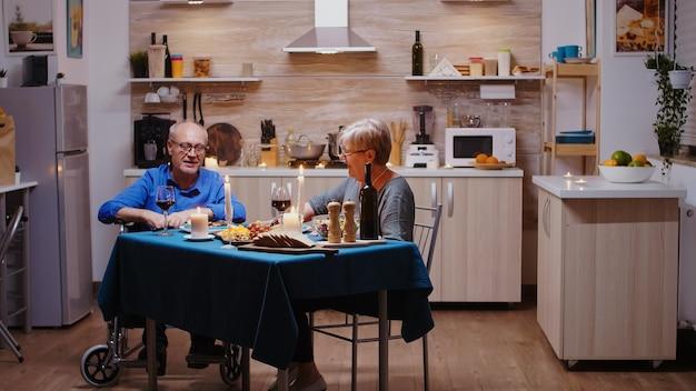 Gelukkige oudere bejaarde vrouw die thuis romantisch diner eet in de gezellige keuken met haar gehandicapte man. geïmobiliseerde verlamde gehandicapte oudere man met romantisch diner.