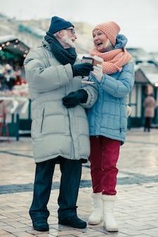 Gelukkige oudere man en vrouw in warme kleren die in de winterdag buiten staan en naar elkaar glimlachen terwijl ze kartonnen kopjes koffie kletteren