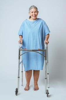 Gelukkige oudere patiënt die een zimmerframe gebruikt