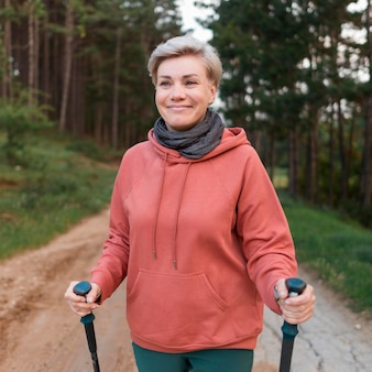 Gelukkige oudere toeristenvrouw in het bos met wandelstokken