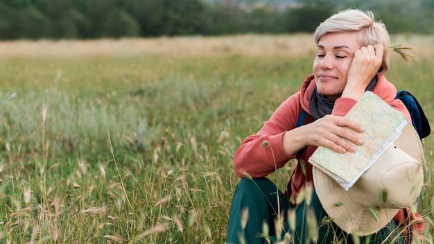 Gelukkige oudere toeristenvrouw in openlucht in aard