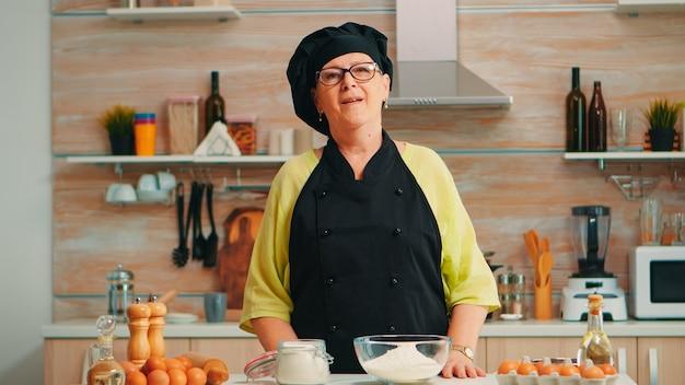 Gelukkige oudere vrouw die bonete draagt en naar de camera in de eetkamer thuis kijkt. gepensioneerde oude bakker met keukenuniform die bakkerijingrediënten op tafel bereidt, klaar om zelfgebakken brood, gebak en pasta te koken.