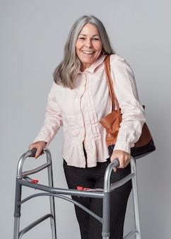 Gelukkige oudere vrouw die een zimmerframe gebruikt