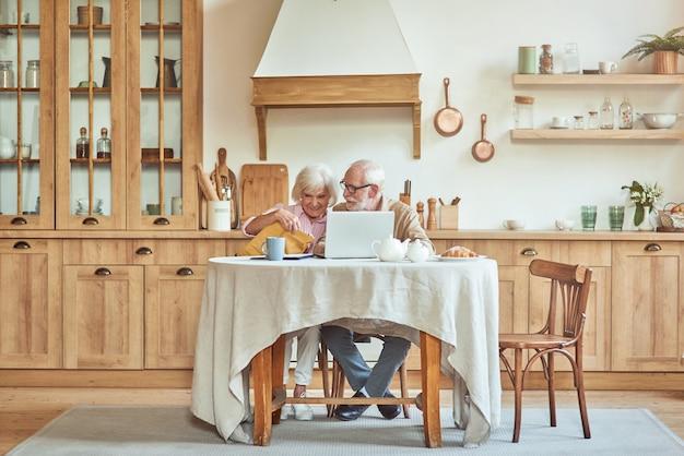 Gelukkige oudere vrouw die envelop met documenten vasthoudt en zit te luisteren naar haar man