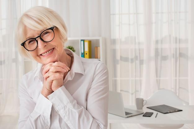 Gelukkige oudere vrouw die zich in haar bureau bevindt