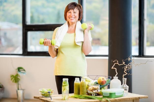 Gelukkige oudere vrouw in sportkleding training met halters binnenshuis met gezond voedsel op tafel