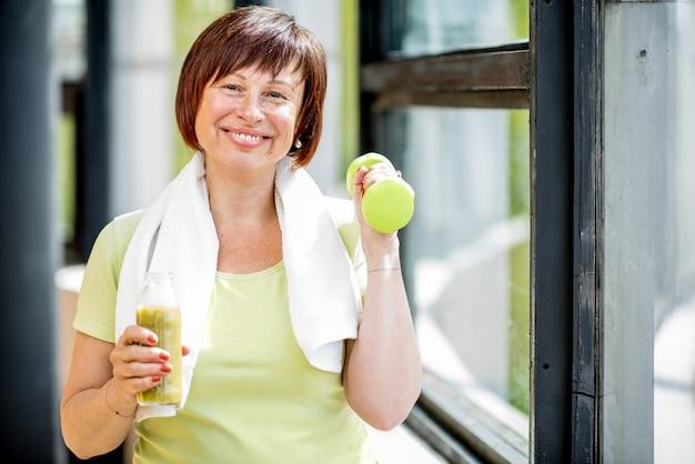 Gelukkige oudere vrouw in sportkleding training met halters binnenshuis op de achtergrond van het raam