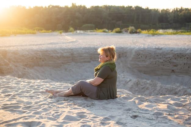 Gelukkige oudere vrouwenzitting op een zand buiten in de zomer
