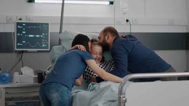 Gelukkige ouders bezoeken zieke dochter die kind knuffelt tijdens ziekteonderzoek