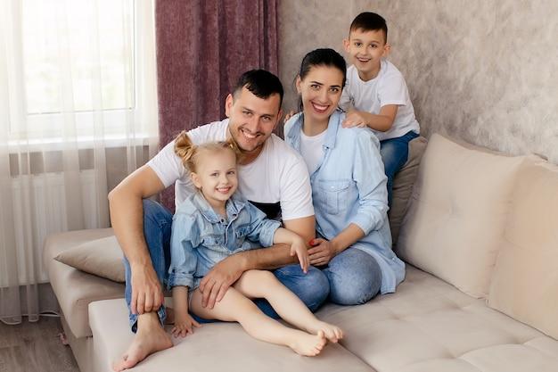 Gelukkige ouders chatten met hun kinderen thuis, samen op de bank in de woonkamer zitten en glimlachen