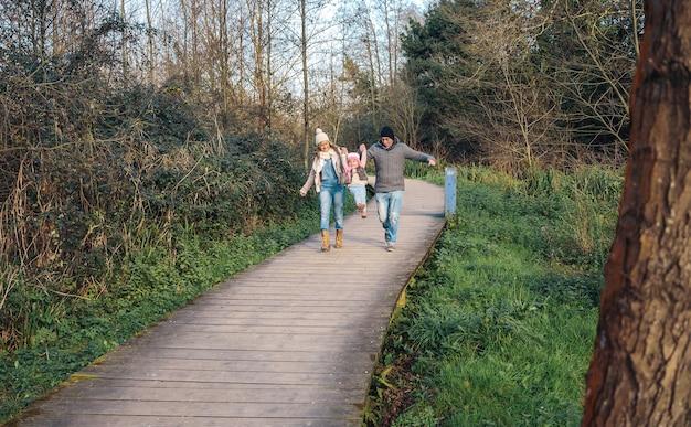Gelukkige ouders die hun dochter bij de hand houden om over een houten pad het bos in te springen