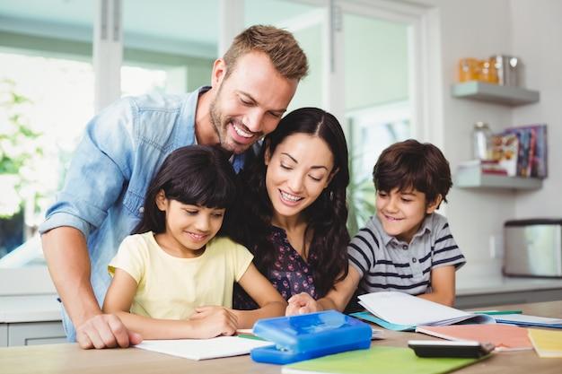 Gelukkige ouders die kinderen helpen die huiswerk doen