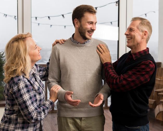 Gelukkige ouders die zoon thuis omhelzen
