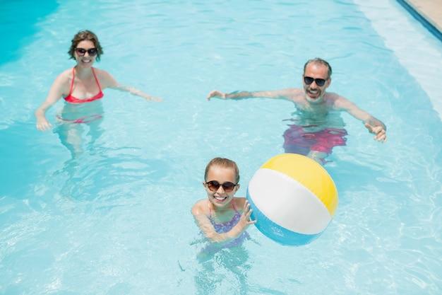 Gelukkige ouders en dochter spelen met bal zwemmen in zwembad