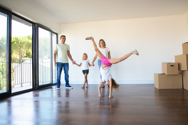 Gelukkige ouders en dochters die housewarming vieren, meisje doet radslag
