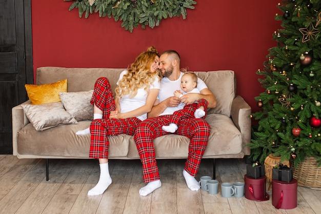 Gelukkige ouders en hun baby zittend op de bank in de buurt van de kerstboom thuis
