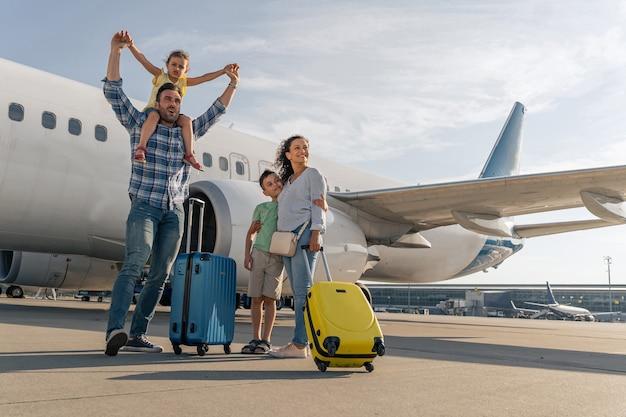 Gelukkige ouders en hun kinderen die wachten om samen te reizen