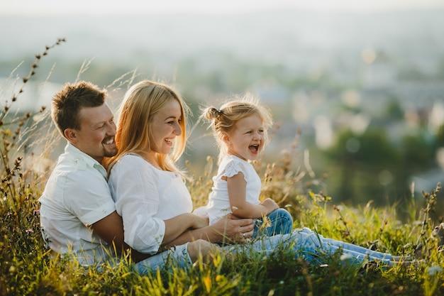 Gelukkige ouders en hun kleine meisje rusten op het gazon in mooie zomerdag