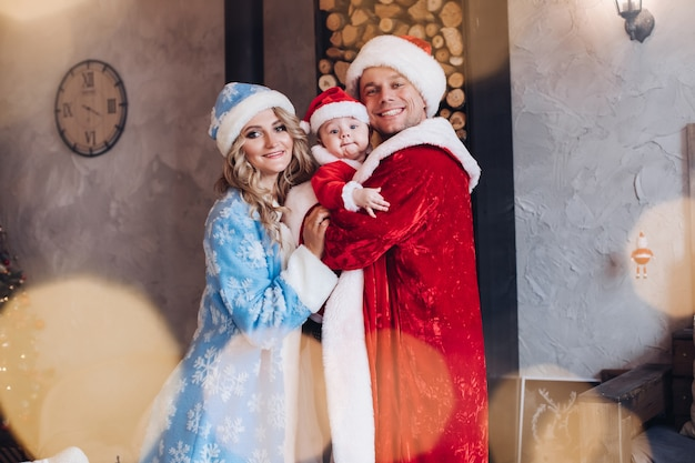 Gelukkige ouders en hun schattige kind gekleed in wamr-jassen die zich in een omhelzing bevinden. vakantie concept