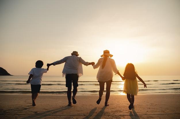 Gelukkige ouders en kind hebben plezier met het spelen van zand in de zomervakantie op het strandreizen