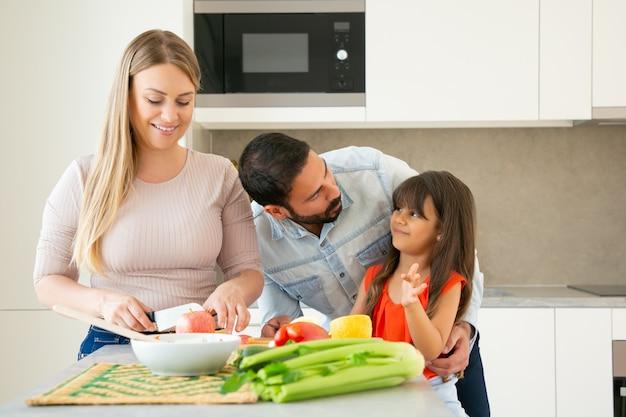 Gelukkige ouders en kind samen koken. meisje chatten en knuffelen met papa terwijl moeder verse groenten en fruit snijdt. familie koken of lifestyle concept