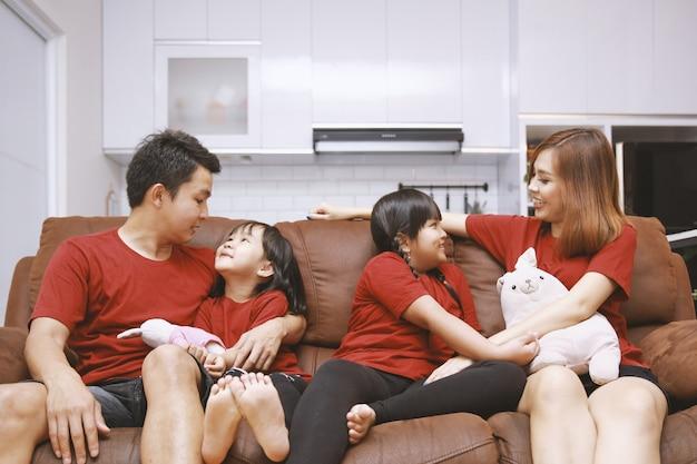 Gelukkige ouders en kinderen die plezier hebben samen op de bank zitten vrolijke jonge paar praten en lachen speelspel met twee kleine dochters in de woonkamer thuis familie grappige activiteit