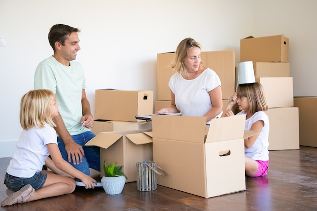Gelukkige ouders en kleine meisjes die plezier hebben tijdens het uitpakken van dingen in een nieuw appartement, zittend op de vloer en objecten uit open dozen halen